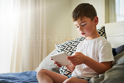 Buy stock photo Shot of a little boy using a digital tablet at home