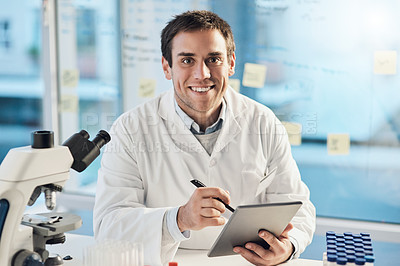 Buy stock photo Cropped portrait of a handsome young male scientist working on a tablet in his lab