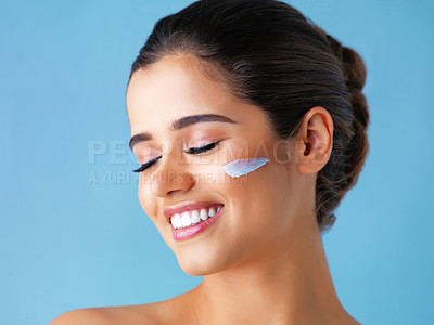 Buy stock photo Studio shot of a beautiful young woman with lotion on her face against a blue background