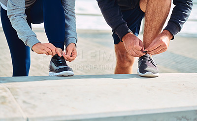 Buy stock photo Closeup shot of a couple tying their shoelaces while exercising outdoors