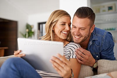 Buy stock photo Cropped shot of a young married couple using a tablet together on the sofa at home