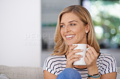 Buy stock photo Shot of an attractive young woman drinking a cup of coffee while relaxing on the sofa at home