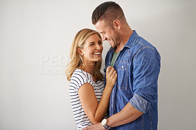 Buy stock photo Shot of a happy and loving young couple embracing each other against a gray wall