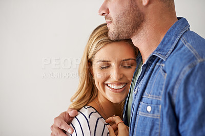 Buy stock photo Shot of a happy and loving young couple standing together against a gray wall