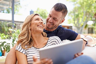 Buy stock photo Cropped shot of an affectionate and happy couple using their tablet while relaxing outside in their backyard