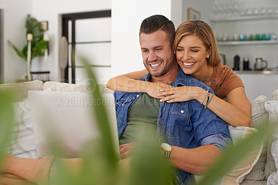 Buy stock photo Shot of an affectionate couple using their laptop while relaxing at home