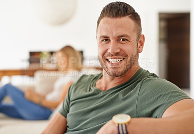 Buy stock photo Cropped shot of a young handsome man chilling on the sofa while his wife is in the background in the living room at home