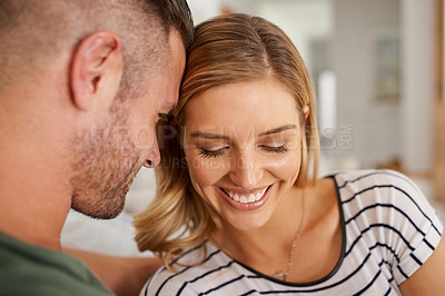Buy stock photo Cropped shot of a young married couple being affectionate on the sofa at home