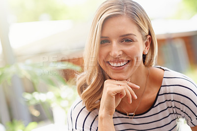 Buy stock photo Cropped portrait of an attractive and happy woman relaxing outdoors in her backyard