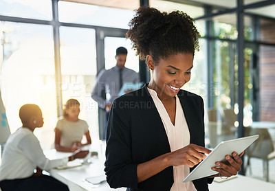 Buy stock photo Shot of a businesswoman using a digital tablet while her colleagues have a meeting in the background