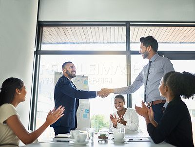 Buy stock photo Shot of two businesspeople shaking hands while in a meeting