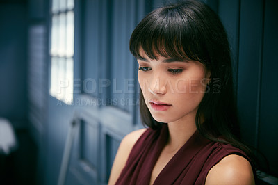 Buy stock photo Cropped shot of a young attractive businesswoman feeling depressed in a corridor at the office
