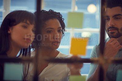 Buy stock photo Cropped shot of young businesspeople brainstorming on a glass wall in the office