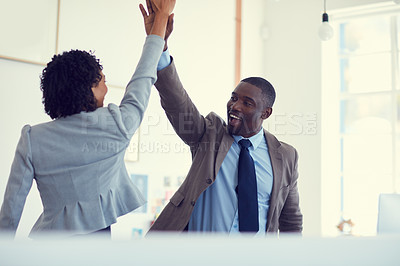 Buy stock photo Cropped shot of a young businessman and businesswoman giving each other a high five in the office
