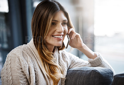 Buy stock photo Cropped shot of a young woman taking a call while relaxing at home