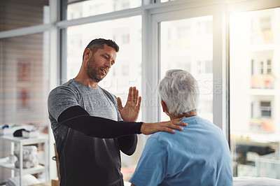 Buy stock photo Shot of a young male physiotherapist assisting a senior patient in recovery