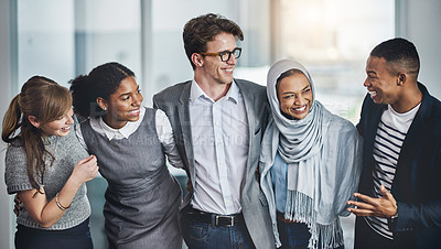 Buy stock photo Shot of a group of young cheerful businesspeople standing with arms around inside of the office at work during the day
