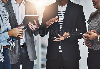 Buy stock photo Shot of a group of unrecognizable businesspeople having a discussion in the office at work during the day