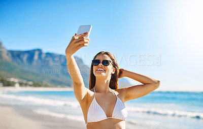 Buy stock photo Shot of a beautiful young woman taking a selfie on the beach
