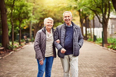 Buy stock photo Cropped portrait of an affectionate senior couple out for a walk in the park