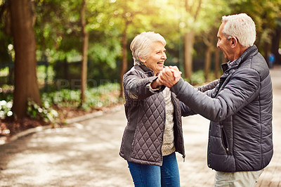 Buy stock photo Cropped shot of an affectionate senior couple dancing in the park