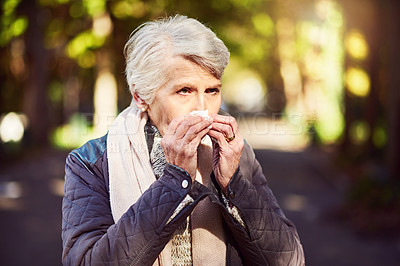 Buy stock photo Cropped shot of a senior woman blowing her nose while out at the park