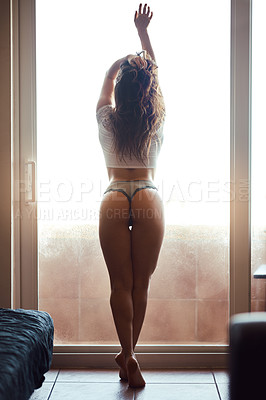 Buy stock photo Rearview shot of an unrecgnizable woman leaning against a glass door at home
