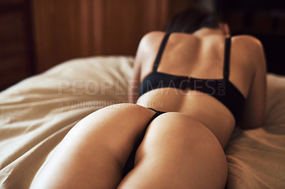 Buy stock photo Rearview shot of an unrecognizable woman in her underwear laying on her bed at home