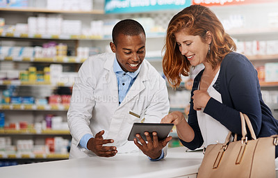 Buy stock photo Shot of a pharmacist showing a customer something on a digital tablet in a chemist