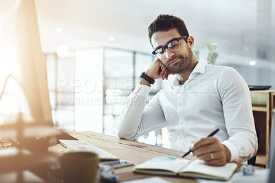 Buy stock photo Shot of a young businessman looking bored while working in an office