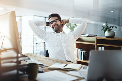 Buy stock photo Shot of a young businessman taking a break while working in an office