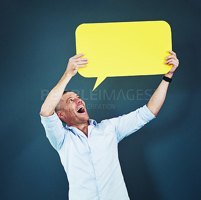 Buy stock photo Studio shot of a man holding a speech bubble against a blue background