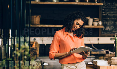 Buy stock photo Shot of a mature woman using a digital tablet while working in a coffee shop