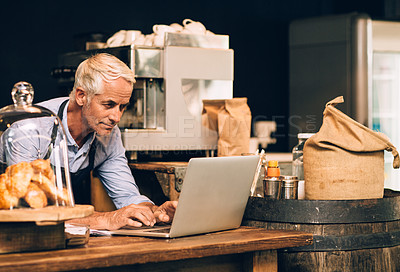Buy stock photo Shot of a mature man using a laptop while working in a coffee shop