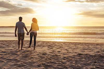 Buy stock photo Shot of a mature couple going for a romantic sunset stroll at the beach