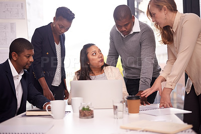 Buy stock photo Shot of a group of young businesspeople using a laptop together in a modern office