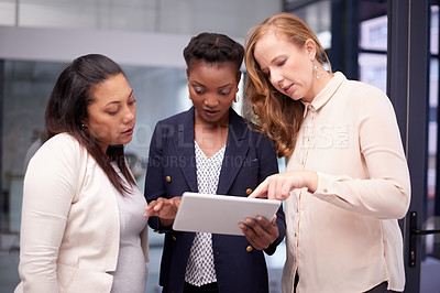 Buy stock photo Shot of a group of young businesswomen using a digital tablet together in a modern office