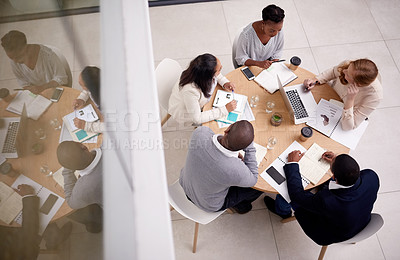 Buy stock photo High angle shot of a group of young businesspeople having a meeting in a modern office