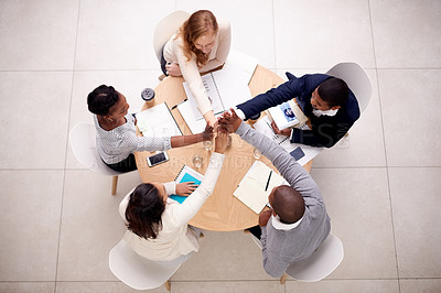 Buy stock photo High angle shot of a group of young businesspeople having a meeting and joining hands in solidarity