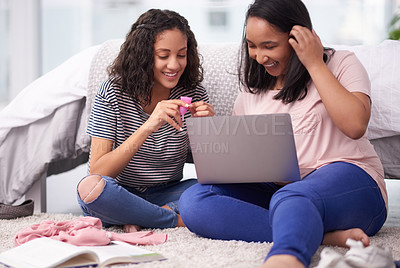Buy stock photo Shot of two teenage girls researching the menstrual cup on a laptop at home