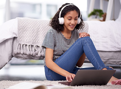 Buy stock photo Shot of a teenage girl listening to music and using a laptop at home