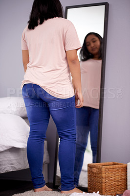 Buy stock photo Shot of a teenage girl looking at her reflection in the mirror at home