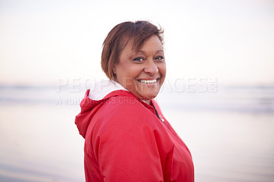 Buy stock photo Portrait of a happy mature woman enjoying a day at the beach