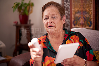 Buy stock photo Shot of a senior woman reading the label on a medicine container while using a digital tablet