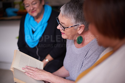 Buy stock photo Shot of senior women reading a book together and having a discussion about it