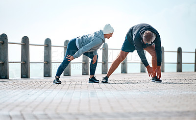Buy stock photo Shot of a mature couple warming up before their run outdoors