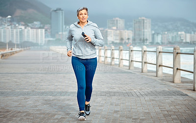 Buy stock photo Shot of a mature woman listening to music while exercising outdoors