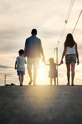 Buy stock photo Rearview shot of an unrecognizable family walking together in the neighbourhood