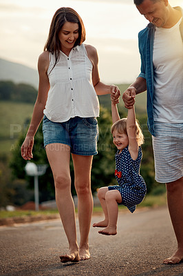 Buy stock photo Shot of a young family walking together in the neighbourhood