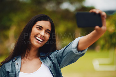 Buy stock photo Shot of an attractive young woman taking selfies using a mobile phone in a park